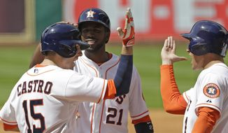 Houston Astros' Jason Castro (15), Dexter Fowler (21) and George Springer celebrate Castro's three-run homer against the Chicago White Sox in the first inning of a baseball game, Saturday, May 17, 2014, in Houston. (AP Photo/Pat Sullivan)
