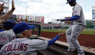 New York Mets' Juan Lagares, right, celebrates with manager Terry Collins (10) and others after his two-run homer during the third inning of a baseball game against the Washington Nationals at Nationals Park Saturday, May 17, 2014, in Washington. (AP Photo/Alex Brandon)