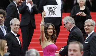 "Actress Salma Hayek holds up a sign reading ""bring back our girls"", part of a campaign calling for the release of nearly 300 abducted Nigerian schoolgirls being held by Nigerian Islamic extremist group Boko Haram, as she arrives for the screening of Saint-Laurent at the 67th international film festival, Cannes, southern France, Saturday, May 17, 2014. (AP Photo/Thibault Camus)"