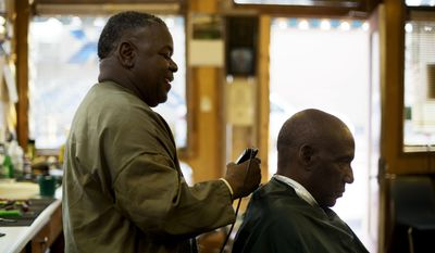 In this April 25, 2014 photo, Gary Roberts, left, cuts the hair of Charles Allen, both lifelong residents, in his barber shop in Montezuma, Ga. Roberts once worked at the now closed Flint River Hospital. Alarmed by hospital closures, health officials in Georgia are changing rules to let stressed rural hospitals become expanded emergency rooms that can also handle routine childbirths or outpatient surgery.  (AP Photo/David Goldman)