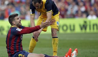 Barcelona's Gerard Pique, left, gestures while Atletico's Diego Godin, from Uruguay listens during a Spanish La Liga soccer match between FC Barcelona and Atletico Madrid at the Camp Nou stadium in Barcelona, Spain, Saturday, May 17, 2014. (AP Photo/Emilio Morenatti)