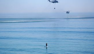 In this May 16, 2014 photo, a paddle boarder watches as two firefighting helicopters take on water from the Pacific Ocean off of San Clemente, Calif. The water-dropping helicopters were part of a larger effort combating three wildfires at the nearby Camp Pendleton Marine base. The fires prompted about 8,400 military personnel and their families to be sent home from various parts of the sprawling coastal base between Los Angeles and San Diego. (AP Photo/Bailey Bianco)