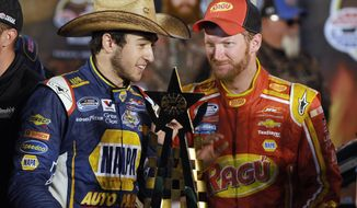 FILE - In this April 4, 2014, photo, Chase Elliott, left, talks with team owner Dale Earnhardt Jr. in Victory Lane after Elliott won the NASCAR Nationwide auto race at Texas Motor Speedway in Fort Worth, Texas. Elliott's driving skills have made it easy to forget he's still in high school. That changes this weekend when the NASCAR Nationwide points leader sandwiches graduation around a trip to Iowa Speedway for a key early-season race.  (AP Photo/Ralph Lauer, File)