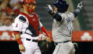 Tampa Bay Rays' Yunel Escobar makes a gesture, after returning to the plate from hitting a solo home run with Los Angeles Angels catcher Hank Conger, left, watching in the fifth inning of a baseball game on Friday, May 16, 2014, in Anaheim, Calif. (AP Photo/Alex Gallardo)