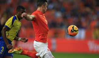 Netherlands' captain Robin van Persie scores 1-1 before Ecuador's Frickson Erazo, left,  can intercept, during the international friendly soccer match between Netherlands and Ecuador at ArenA stadium in Amsterdam, Netherlands, Saturday, May 17, 2014. (AP Photo/Peter Dejong)