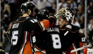 Anaheim Ducks right wing Teemu Selanne, middle, is greeted by center Ryan Getzlaf, left, and goalie Jonas Hiller after their loss against the Los Angeles Kings during Game 7 of an NHL hockey second-round Stanley Cup playoff series in Anaheim, Calif., Friday, May 16, 2014. (AP Photo/Chris Carlson)