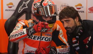 Spanish MotoGP rider Marc Marquez of the Repsol Honda Team has a talk with team members during the last free practice session of the MotoGP World Championship at the Bugatti race track in Le Mans, western France, Saturday, May 17, 2014. The race will start Sunday. (AP Photo/David Vincent)