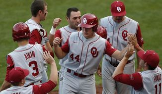Oklahoma's Austin O'Brien, center front, and Anthony Hermelyn, center rear, are greeted at the dugout after scoring against Oklahoma State during an NCAA college baseball game in Tulsa, Okla., on Saturday, May 17, 2014. (AP Photo/Tulsa World, Matt Barnard)