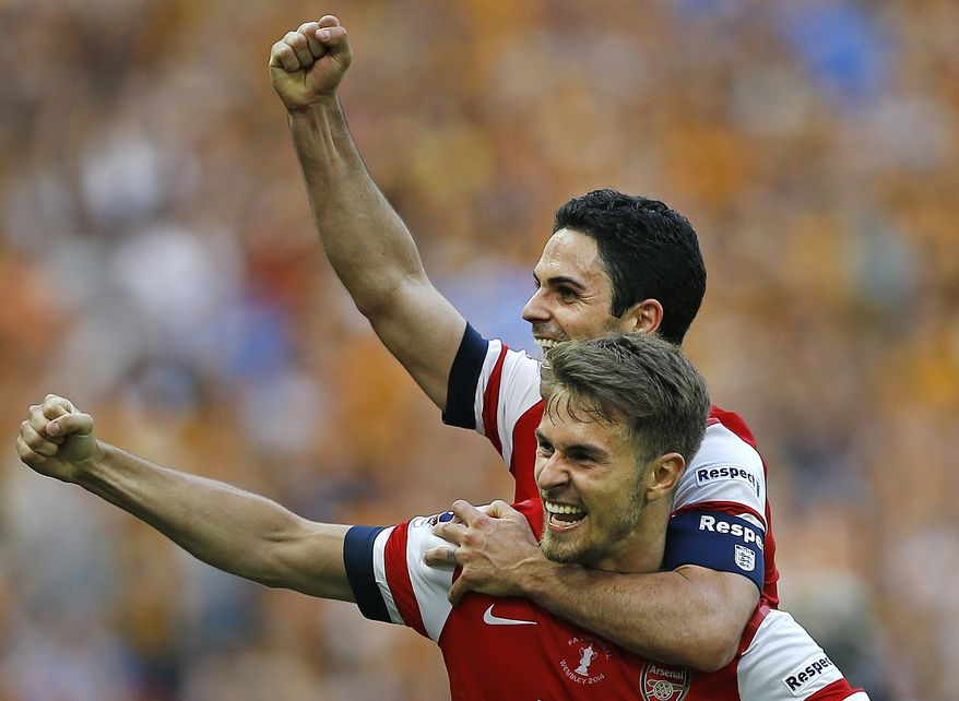 Arsenal's Aaron Ramsey, front, celebrates with Mikel Arteta after his team won the English FA Cup final soccer match between Arsenal and Hull City at Wembley Stadium in London, Saturday, May 17, 2014. Arsenal won 3-2 after extra-time. (AP Photo/Kirsty Wigglesworth)