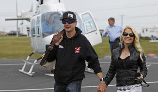 Kurt Busch walk with his girlfriend, Patricia Driscoll, after arriving for the NASCAR Sprint All-Star auto race at Charlotte Motor Speedway in Concord, N.C., Saturday, May 17, 2014. Busch qualified earlier Saturday for the Indianapolis 500. (AP Photo/Terry Renna)