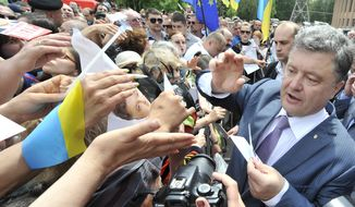 Ukrainian presidential candidate Petro Poroshenko, right, is welcomed by his supporters during a rally  in Kruvuy Rig, Ukraine, Saturday, May 17, 2014. A Presidential vote in Ukraine is scheduled for May 25. (AP Photo/Mykola Lazarenko, Pool)