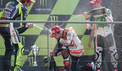 Italian MotoGP rider Valentino Rossi, rear left, and Spanish MotoGP rider Alvaro Bautista, rear right, spray champagne to winner Marc Marquez, of Spain, down on knee, center, on the podium of the MotoGP World Championship race at the Bugatti race track in Le Mans, western France, Sunday, May 18, 2014. (AP Photo/David Vincent)