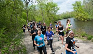 More then three hundred attendees run through the Nichols Arboretum in Ann Arbor as they take part in the first Paul Dewolf Memorial Hero Run, Sunday, May 18, 2014. The race is in honor of slain University of Michigan medical student Paul DeWolf.  (AP Photo/The Ann Arbor News, Courtney Sacco)