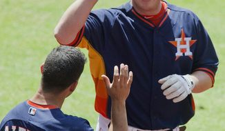 Houston Astros' Matt Dominguez celebrates with teammate Jose Altuve (27) after hitting his second home run of the baseball game against the Chicago White Sox in the fifth inning, Sunday, May 18, 2014, in Houston. (AP Photo/The Courier, Jason Fochtman)