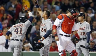 Detroit Tigers' Victor Martinez (41) celebrates his two-run home run that also drove in Miguel Cabrera (24) as Boston Red Sox's A.J. Pierzynski, second from right, looks down, in the third inning of a baseball game in Boston, Sunday, May 18, 2014. (AP Photo/Michael Dwyer)