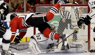 Chicago Blackhawks' Jonathan Toews (19)  flies over Los Angeles Kings goalie Jonathan Quick (32) during the second period in Game 1 of the Western Conference finals in the NHL hockey Stanley Cup playoffs in Chicago on Sunday, May 18, 2014. The Blackhawks won 3-1. (AP Photo/Nam Y. Huh)