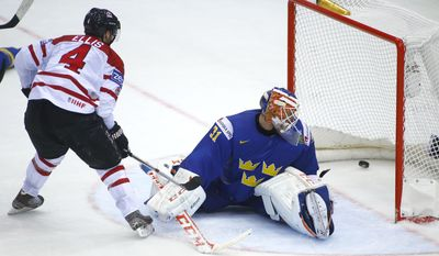Canada's Ryan Ellis, left, scores past Sweden's Anders Nilsson during the Group A preliminary round match at the Ice Hockey World Championship in Minsk, Belarus, Sunday, May 18, 2014. (AP Photo/Sergei Grits)