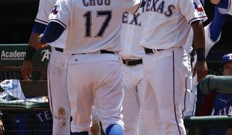 Texas Rangers' Shin-Soo Choo (17) is congratulated by Elvis Andrus, right, after scoring a run on a triple hit by Alex Rios against the Toronto Blue Jays during the fourth inning of a baseball game, Sunday, May 18, 2014, in Arlington, Texas. (AP Photo/Jim Cowsert)