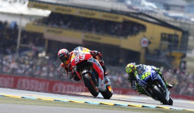 Spanish MotoGP rider Marc Marquez of the Repsol Honda Team leads the race ahead of Italian MotoGP rider Valentino Rossi of Movistar Yamaha Team, right, during the MotoGP World Championship race at the Bugatti race track in Le Mans, western France, Sunday, May 18, 2014. (AP Photo/David Vincent)