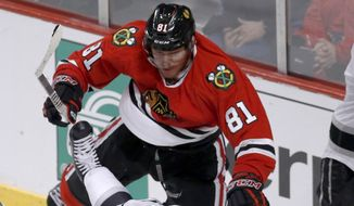 Chicago Blackhawks right wing Marian Hossa (81) checks Los Angeles Kings right wing Dustin Brown (23) behind the net during the third period of Game 1 of the Western Conference finals in the NHL hockey Stanley Cup playoffs in Chicago on Sunday, May 18, 2014. The Blackhawks won 3-1. (AP Photo/Charles Rex Arbogast)