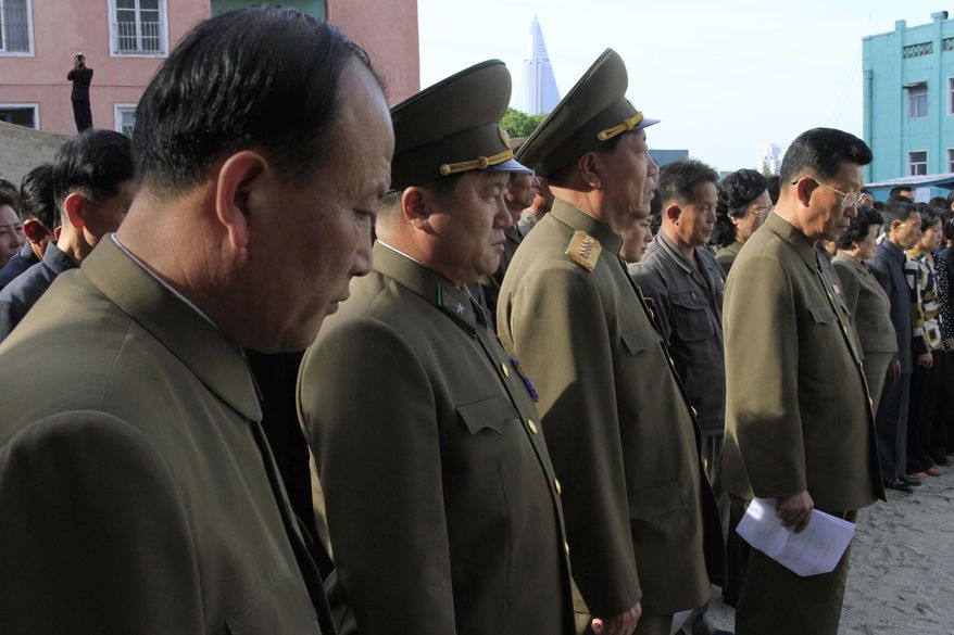"""In this Saturday, May 17, 2014 photo, North Korean officials stand among the families of victims of an accident at an apartment construction site in Pyongyang, North Korea, during a gathering in the capital where senior officials apologized and took responsibility. The word of the collapse in the secretive nation's capital was reported Sunday morning by the North's official Korean Central News Agency, which gave no death toll but said that the accident was """"serious"""" and upset North Korea's leader, Kim Jong Un. (AP Photo/Kim Kwang Hyon)"""