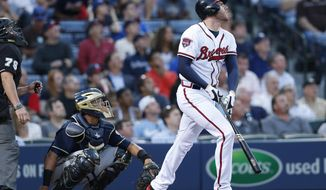 Atlanta Braves first baseman Freddie Freeman (5) follows through with a solo-home run as Milwaukee Brewers catcher Martin Maldonado (12) looks on in the third inning of a baseball game Monday, May 19, 2014 in Atlanta. (AP Photo/John Bazemore)