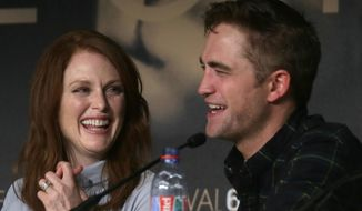 Actress Julianne Moore, left, and actor Rob Pattinson laugh during a press conference for Maps to the Stars at the 67th international film festival, Cannes, southern France, Monday, May 19, 2014. (AP Photo/Virginia Mayo)