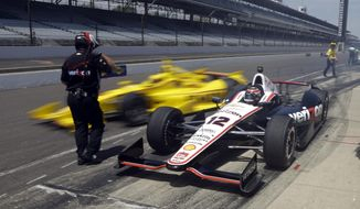Will Power, (12) of Australia, waits as teammate Helio Castroneves, of Brazil, pulls out around him as they leave the pit area during practice for the Indianapolis 500 IndyCar auto race at the Indianapolis Motor Speedway in Indianapolis, Monday, May 19, 2014. (AP Photo/Michael Conroy