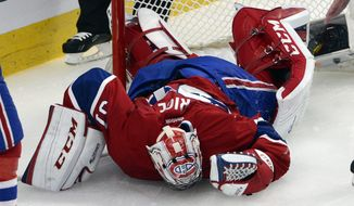 In this photo taken May 17, 2014,  Montreal Canadiens goalie Carey Price (31) lies on the ice after being run into by New York Rangers' Chris Kreider during the second period in Game 1 of the NHL hockey Eastern Conference final Stanley Cup playoff series in Montreal.  Price's status for Game 2 of the Eastern Conference final is still unclear. Price briefly tested his right knee Sunday before the Canadiens' optional practice. Coach Michel Therrien said the team will know more Monday before they host the New York Rangers trailing 1-0 in the series. (AP Photo/The Canadian Press, Ryan Remiorz)