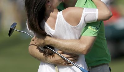 Brendon Todd is kissed by his wife, Rachel, on the 18th green after winning the Byron Nelson Championship golf tournament, Sunday, May 18, 2014, in Irving, Texas. (AP Photo/Tony Gutierrez)
