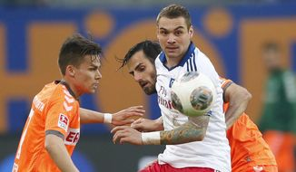 Hamburg's Pierre-Michel Lasogga, center, Fuerth's Zoltan Stieber, left, and Fuerth's Mergim Mavraj challenge for the ball during their 1st leg relegation soccer match between Hamburger SV and Greuther Fuerth in Hamburg, Germany, Thursday, May 15, 2014.  (AP Photo/Matthias Schrader)