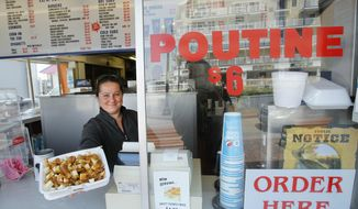 FILE - In this May 26, 2011, file photo, Karen Ramunno of Ramunno's Pizza and Grill, delivers an order of poutine, a french fry, gravy and cheese dish popular with Canadians, at Old Orchard Beach, Maine. Poutine is one of the 150 new words appearing in Merriam-Webster's Collegiate Dictionary and the company's free online database. (AP Photo/Robert F. Bukaty, File)