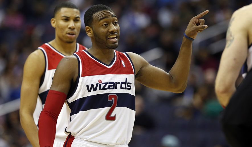 Washington Wizards guard John Wall (2) directs his teammates in the first half of an NBA basketball game against the Denver Nuggets Monday, Dec. 9, 2013 in Washington. (AP Photo/Alex Brandon)