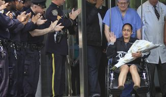 NYPD Officer Rosa Rodriguez, right, is pushed in a wheelchair as she leaves Weill Cornell Medical Center to cheers and applause from fellow officers, Monday May 19, 2014, in New York. Rodriguez was severely injured while responding to a fire which killed her partner. The officers were overcome by smoke at a Coney Island housing project. (AP Photo/Bebeto Matthews)