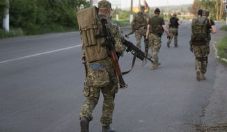 FILE - In this Saturday May 17, 2014 file photo pro-Russian militants walk to their positions to fight against Ukrainian government troops at a checkpoint blocking the major highway which links Kharkiv, outside Slovyansk, eastern Ukraine. The struggling interim government in Kiev has been counting on the election to install a president who would be seen as a legitimate successor to Viktor Yanukovych, who fled to Russia in February after months of street protests. But the long-anticipated election may not be considered legitimate by Russia, the West or Ukrainians themselves if people in a large part of the country are unable or unwilling to cast their ballots. (AP Photo/Alexander Zemlianichenko, file)