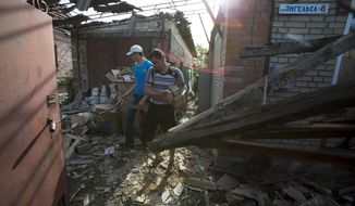 Relatives of Yekaterina Len, 61, try to clean debris in her destroyed house following a shelling in Slovyansk, eastern Ukraine, Tuesday, May 20, 2014. Slovyansk has been the major fighting ground between pro-Russian insurgents and Ukrainian government troops in eastern Ukraine. (AP Photo/Alexander Zemlianichenko)