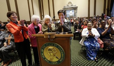 New Washington state Supreme Court Justice Mary Yu, right, holds her hands in front of her as she is applauded by friends Anne Levinson, left, Ruth Woo and Phyllis Gutierrez Kenney following her swearing-in to the bench Tuesday, May 20, 2014, in Olympia, Wash. Yu, a former King County Superior Court judge, was sworn in as the newest member of the court, marking the first time the high court has had an openly gay justice. Yu, whose mother is from Mexico and father is from China, is also the first Asian American and first female Hispanic member of the court. (AP Photo/Elaine Thompson)
