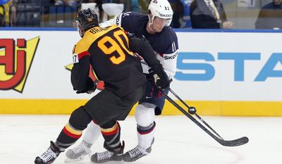 Germany defender Constantin Braun, left, battles for the puck with USA forward Brock Nelson during the Group B preliminary round match between USA and Germany at the Ice Hockey World Championship in Minsk, Belarus, Tuesday, May 20, 2014. (AP Photo/Darko Bandic)