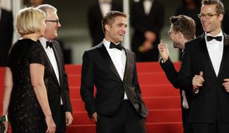 From left, producer Liz Watts, producer David Linde, actor Robert Pattinson, director David Michod, and actor Guy Pearce laugh as they pose for photographers as they arrive for the screening of The Rover at the 67th international film festival, Cannes, southern France, Sunday, May 18, 2014. (AP Photo/Thibault Camus)