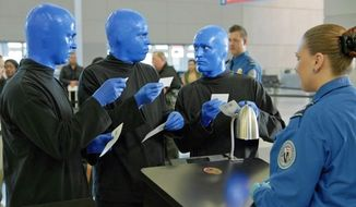 In this frame from video provided by R&R Partners and released in May 2014, Las Vegas performers Blue Man Group present documents to a Transportation Security Administration official in one of eight funny videos that play at security checkpoints at Las Vegas' McCarran International Airport. Tourism officials released the humorous new videos illustrating TSA policies as travelers wait for screenings. Other videos feature Las Vegas comedians Carrot Top, Louie Anderson, ventriloquist Terry Fator, among others. They address TSA procedures for liquids, gels and aerosols, metals and electronics, carry-on luggage, strollers, weapons and more. (AP Photo/R&R Partners)