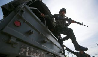 A Thai soldier jumps off a military truck after arriving at a pro-government rally site on the outskirts of Bangkok Tuesday. Thailand's army declared martial law before dawn Tuesday in a surprise announcement it said was aimed at keeping the country stable. (Associated Press)
