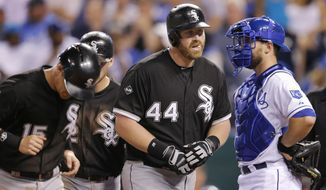 Chicago White Sox designated hitter Adam Dunn (44) leads teammates Gordon Beckham (15) and Conor Gillaspie, back, past Kansas City Royals catcher Brett Hayes after his three-run home run during the eighth inning of a baseball game at Kauffman Stadium in Kansas City, Mo., Tuesday, May 20, 2014. (AP Photo/Orlin Wagner)