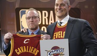 Cleveland Cavaliers general manager David Griffin, left, holds a Cavaliers jersey with the No. 1 displayed on it as he poses for a photo with Cavaliers minority owner Jeff Cohen following the NBA basketball draft lottery in New York, Tuesday, May 20, 2014. The Cavaliers continued their remarkable lottery luck Tuesday, winning the No. 1 pick in the NBA draft for the second straight year. (AP Photo/Kathy Willens)