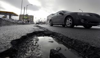 FILE - In this Feb. 11, 2014 file photo a car drives by a pothole in Detroit. The state House's vote to slowly raise gasoline taxes over time if prices increase has senators asking: Is it enough to fix Michigan's deteriorating roads? Talks are underway on whether lawmakers can capitalize on voter anger over shoddy roads and commit to a much higher tax increase, phased in over a handful of years. (AP Photo/Carlos Osorio, File)