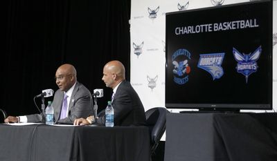 Charlotte Hornets president Fred Whitfield, left, answers a question as Marketing Officer Pete Guelli, right, listens during a news conference to announce officially changing the NBA basketball team's name from Bobcats to Hornets in Charlotte, N.C., Tuesday, May 20, 2014. (AP Photo/Chuck Burton)