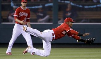 Los Angeles Angels shortstop Erick Aybar, right, can't get a glove on a single by Houston Astros' Chris Carter as Grant Green looks on during the third inning of a baseball game in Anaheim, Calif., Monday, May 19, 2014. (AP Photo/Chris Carlson)