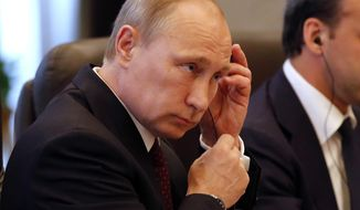 Russia's President Vladimir Putin puts on an earphone during his meeting with China's President Xi Jinping, ahead of the Conference on Interaction and Confidence Building Measures (CICA) in Shanghai, China Tuesday, May 20, 2014. (AP Photo/Carlos Barria, Pool)