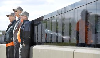 In this photo taken on May 15, 2014, 174th Fighter Squadron Vietnam War veterans, from left, Gordon Young of Sioux City, Lloyd Pippett of Sioux City and Dudley Smidt of Colorado Springs, stand against the memorial wall at the Siouxland Freedom Park  in South Sioux City, Neb. A group of Vietnam War veterans from Sioux City's 174th Tactical Fighter Squadron - the unit now known as the 185th Air Refueling Wing -  toured the replica of the Vietnam Veterans Memorial. (AP Photo/The Sioux City Journal, Tim Hynds) NO SALES, MAGS OUT, TV OUT