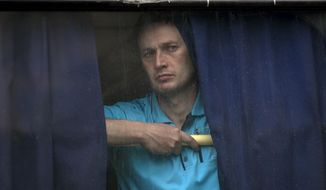 A man looks out of the back window of a bus in Donetsk, Ukraine, Monday May 19, 2014. Ukraine will hold presidential elections on May 25. (AP Photo/Vadim Ghirda)
