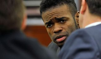 "Jason Omar Griffith, center, looks to his defense attorneys, Abel Yanez, left, and Jeff Banks, in court during his murder trial the Regional Justice Center on Monday, May 19, 2014, in Las Vegas. Griffith is accused of killing Luxor ""Fantasy"" dancer Deborah Flores Narvaez in December 2010. (AP Photo/Las Vegas Review-Journal, David Becker)"